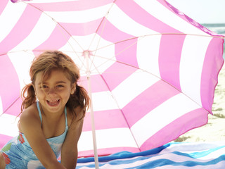 Girl (3-5) in swimsuit on beach by parasol, smiling, portrait