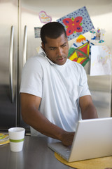 Young man in kitchen on mobile phone with laptop computer