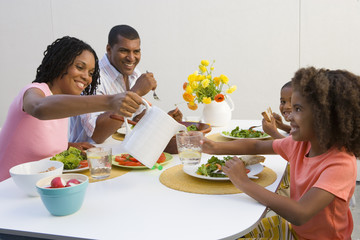 Family of four at dinner table, mother pouring water for daughter (7-9)