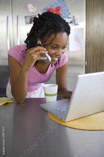 Young woman in kitchen on mobile phone with laptop computer