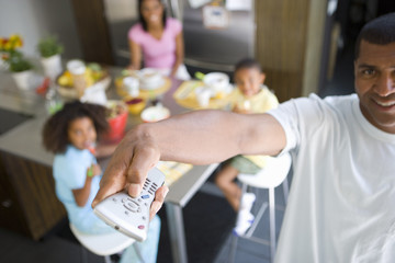 Man using remote control, family at breakfast table in background