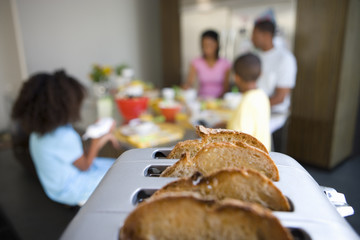 Bread in toaster, family at breakfast table in background