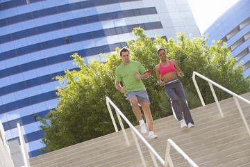 Young man and woman running down steps (tilt)