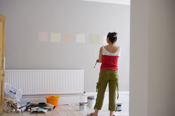 Woman looking at colour samples painted on wall, rear view