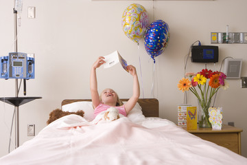 Girl (5-7) reading card in hospital bed