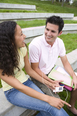 Young couple sharing MP3 player outdoors, smiling at each other