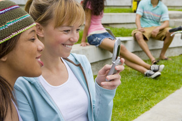 Teenage girls (15-17) using mobile phone outdoors, smiling