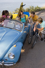 Men on bicycles in conversation with women in convertible car