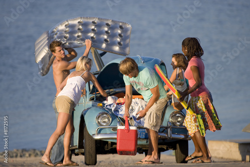 Young men and women unloading car at beach