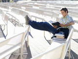 Male student on bench reading