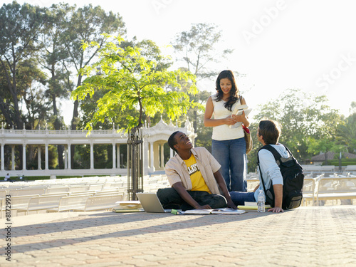 Female student smiling at male students studying outdoors