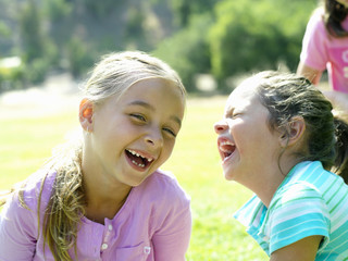Girl and friend (6-8) laughing on grass, close-up