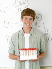 Boy (10-12) with chemistry samples by whiteboard, portrait