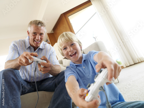 Father and son (8-10) playing video game, portrait, low angle view