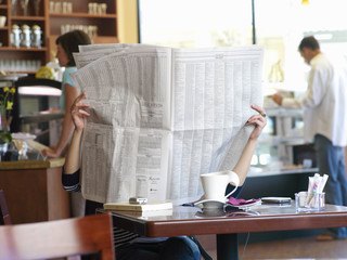 Woman with face obscured by newspaper in cafe