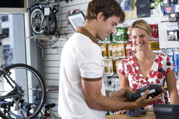 Storekeeper serving customer in shop, smiling