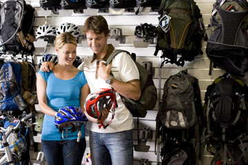 Young couple looking at bicycle helmets in shop