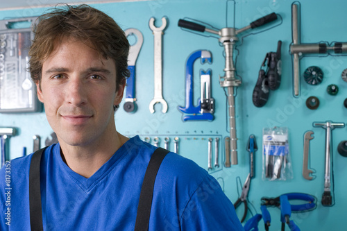 Man by tools hanging on wall, smiling, portrait