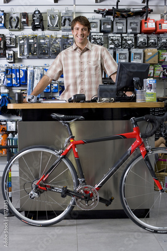 Man behind counter in bicycle shop, smiling, portrait