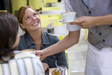 Waiter serving coffee to young couple at table outdoors
