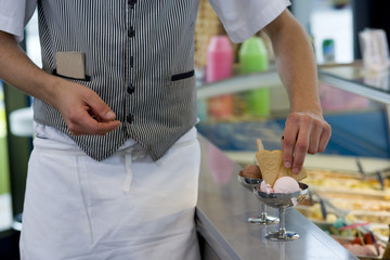 Waiter preparing ice cream dessert, mid section