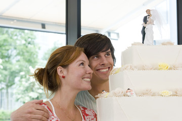Young couple looking at wedding cake, smiling