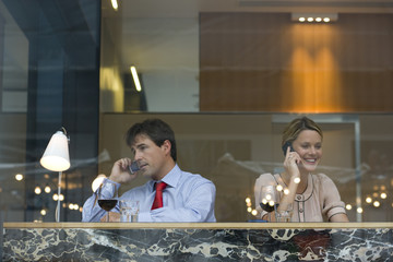 Businessman and woman drinking wine in bar, on mobile phones