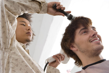 Hairdresser drying client's hair