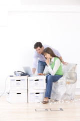 Man and woman working amidst boxes