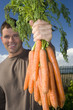 Man with bunch of carrots, portrait