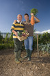Father and son with vegetables in garden, portrait