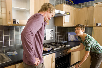Couple in kitchen, woman opening oven