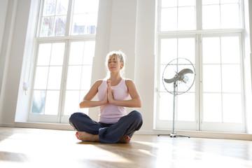 Woman meditating, low angle view