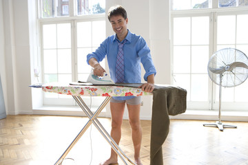 Man ironing trousers, smiling, portrait