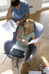 Couple with paperwork, woman with laptop computer in armchair