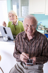 Senior couple with laptop computer and electronic organiser, portrait
