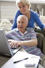 Senior couple with laptop computer in living room