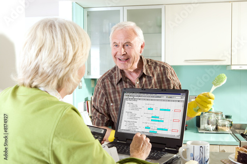 Senior couple smiling at each other, woman using computer