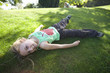 Girl (8-10) laying on grass, portrait
