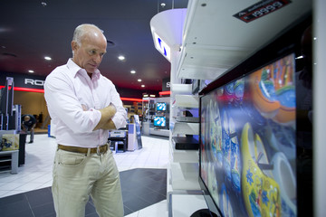 Senior man shopping, by flat screen in electronics shop