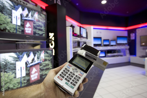 Man with credit card machine in shop, close-up