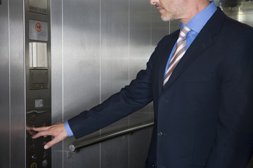 Businessman pressing button in elevator, mid section