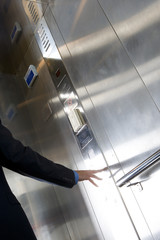 Businessman pressing button in elevator, section