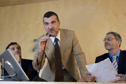 Businessman speaking into microphone, flanked by colleagues