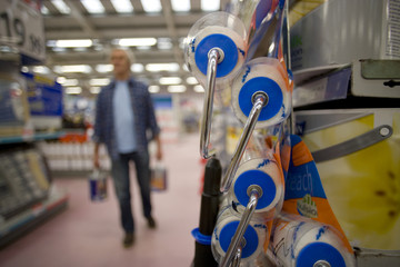 Man in hardware store, close-up of paint rollers