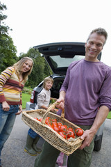 Man with basket of tomatoes by family and car, smiling