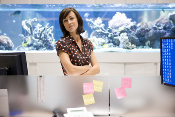 Woman by workstation, fish tank in background, portrait