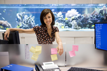Woman by workstation, fish tank in background, smiling, portrait