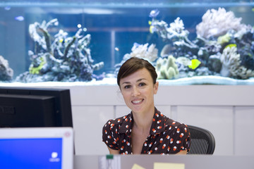 Woman at workstation, fish tank in background, smiling, portrait