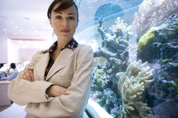 Businesswoman by fish tank, arms crossed, portrait